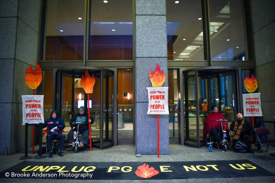 Front doors to PG&E headquarters blocked by four activists on scooters and sitting. Huge banner on ground in front of them reads Unplug PG&E Not Us. Disability justice club
